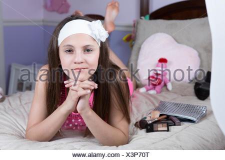 Ritratto di una ragazza distesa sul suo letto con il make-up Foto Stock