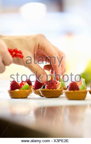 Baker rendendo crostate di frutta in cucina Foto Stock