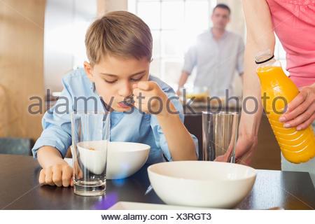 Sezione mediana della donna con bottiglia di succo di frutta in piedi dal figlio avente la colazione con uomo sullo sfondo Foto Stock