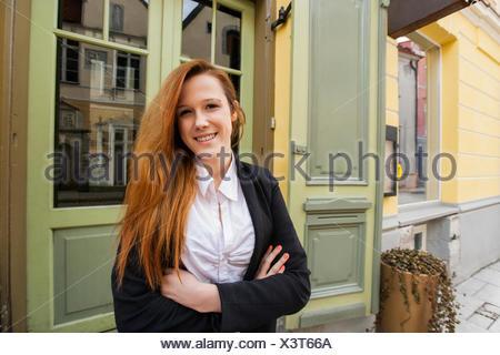 Ritratto di felice proprietario di sesso femminile in piedi con le braccia incrociate fuori del ristorante Foto Stock