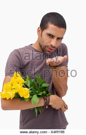 Uomo bello soffia un bacio e tenendo le rose Foto Stock