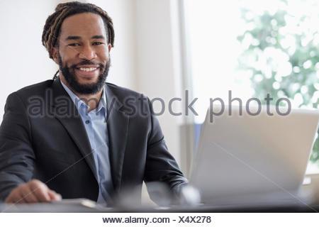 Imprenditore Smiley seduto alla scrivania con computer portatile Foto Stock