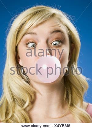 Ragazza bolla di soffiaggio e cross eyed Foto Stock