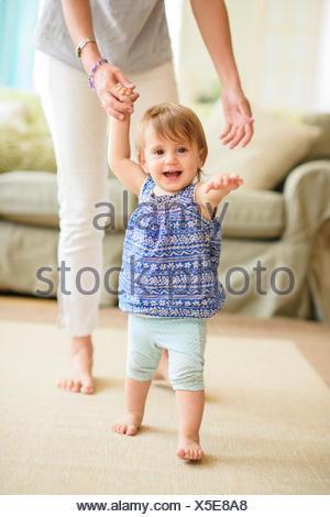 Madre assistere bimba (18-23 mesi) con i suoi primi passi Foto Stock
