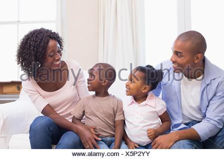 La famiglia felice seduta sul divano insieme Foto Stock