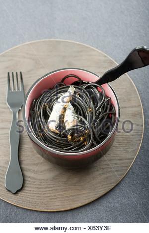 Gli spaghetti al nero di sardine e di Espelette pepe Foto Stock