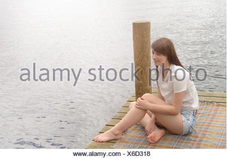 Giovane donna seduta alla fine di un pontile sul lago Foto Stock
