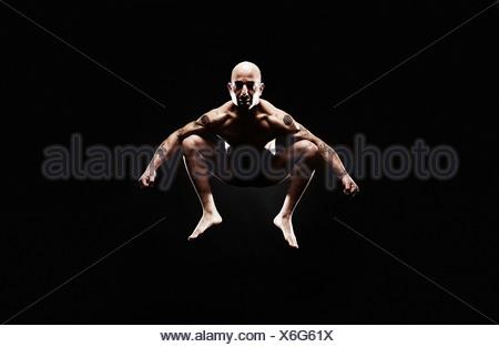 Uomo maturo jumping metà aria Foto Stock