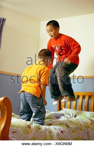 Fratelli africani saltando sul letto Foto Stock