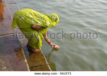 Donna che le offerte per il santo Gange come parte del suo pellegrinaggio a Varanasi, Uttar Pradesh, India, Asia Foto Stock