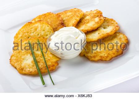 Frittelle di patate con panna acida su sfondo bianco Foto Stock