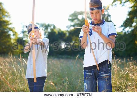 Due giovani ragazzi azienda arco e frecce Foto Stock