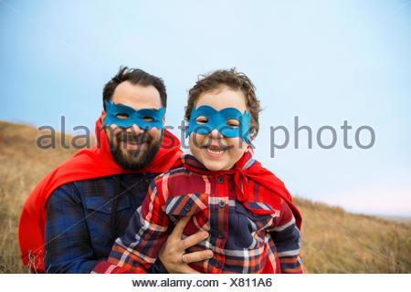 Ritratto di padre e figlio in supereroe capes Foto Stock