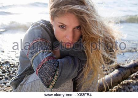 Donna seduta su windy beach Foto Stock