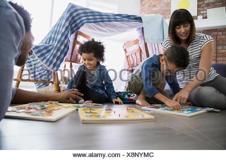 La famiglia gioca con i puzzle sul pavimento Foto Stock