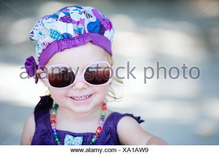 Ritratto di una bambina che indossa gli occhiali da sole e vestiti di fantasia Foto Stock