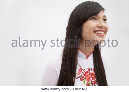 Ritratto di sorridente giovane donna con capelli lunghi che indossa un abito tradizionale dal Vietnam, studio shot Foto Stock