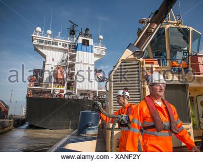 Lavoratori sul rimorchiatore tirando in corda Foto Stock