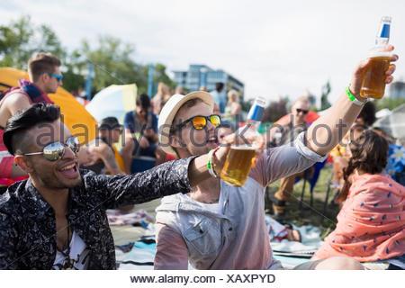 I giovani uomini a bere birra rasserenante al festival musicale estivo Campeggio Foto Stock