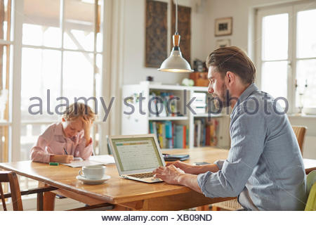 Padre e figlio che lavorano in ufficio in casa Foto Stock