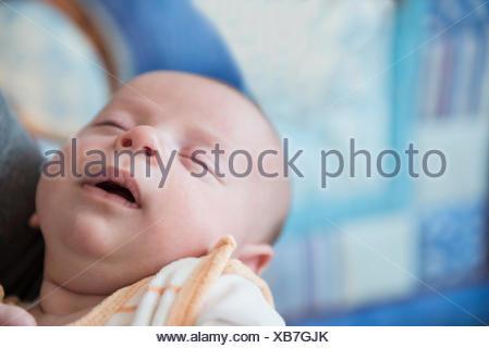 Baby boy dormire nelle braccia del padre, close up Foto Stock