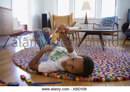 Ragazzo giocando con Toy piano su rug Foto Stock