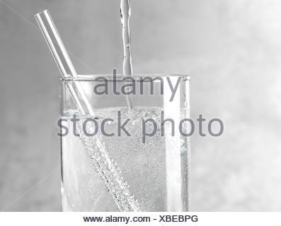 Dettaglio di acqua frizzante è versata in un vetro trasparente con una cannuccia trasparente su un metallo grigio Sfondo. Foto Stock