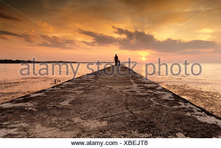 Silhouette di un uomo e suo figlio in piedi alla fine di un pontile, Port Dickson, Malaysia Foto Stock