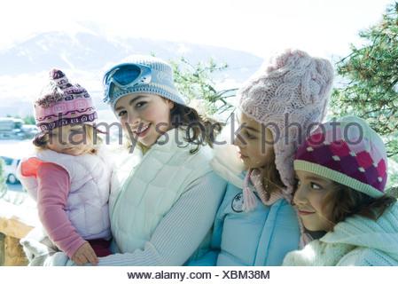 Tre teen o preteen ragazze con bambino in montagna, tutti indossano cappotti invernali e cappelli, ritratto Foto Stock