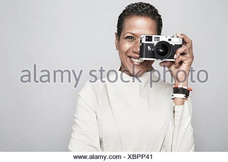 Ritratto in studio di Felice donna matura mantenendo la fotocamera Foto Stock