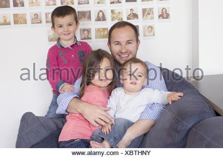 Padre e bambini seduti insieme sul divano, ritratto Foto Stock