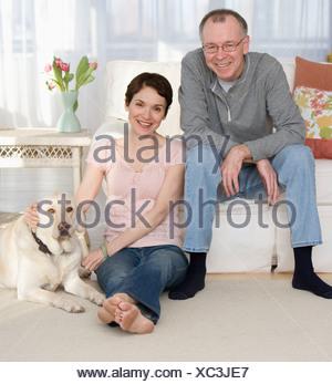 Ritratto di giovane con cane in livingroom Foto Stock