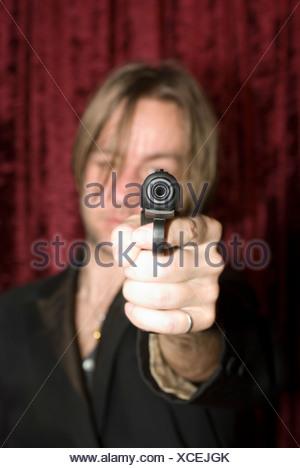 Un uomo che ha di mira una pistola Foto Stock
