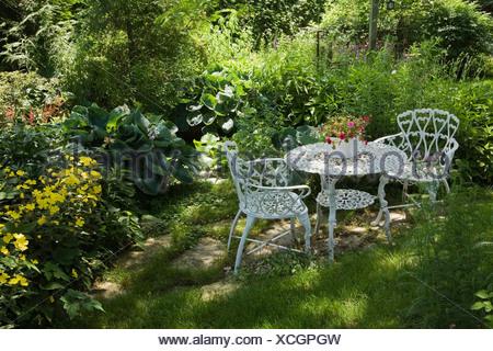 Metallo bianco tavolo e sedie da giardino in una zona residenziale di backyard Foto Stock