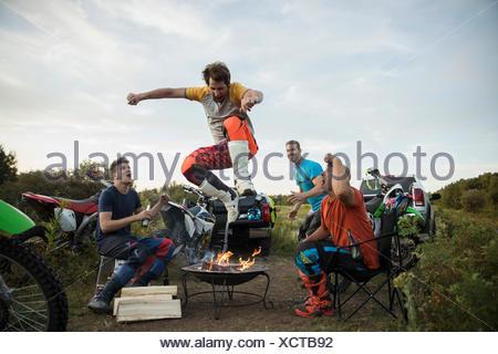Gli amici a guardare l uomo saltando il fuoco nei pressi di motociclette Foto Stock