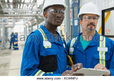 I lavoratori di sesso maschile rivedere documenti all impianto di gas Foto Stock