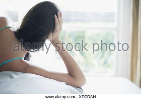 Donna sdraiata sul letto rilassante Foto Stock