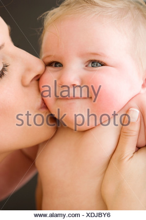 Madre kissing baby la guancia Foto Stock