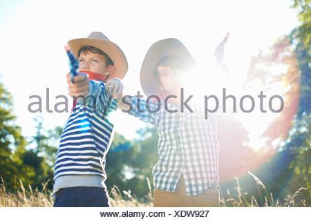 Due giovani ragazzi vestito da cowboy, tenendo pistole giocattolo Foto Stock