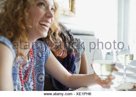 Amici di sesso femminile di ridere mentre dining out Foto Stock