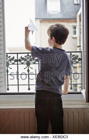 Ragazzo il lancio di aeroplano di carta da finestra Foto Stock