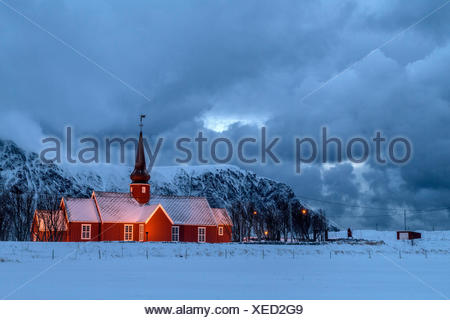 Luci su la Chiesa al tramonto con le vette dolomitiche innevate sullo sfondo Flakstad Isole Lofoten in Norvegia Europa Foto Stock