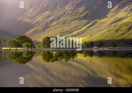 Riflessioni sulla riva del Buttermere all'alba Cumbria Distretto dei Laghi Cumbria Inghilterra England Regno Unito Foto Stock