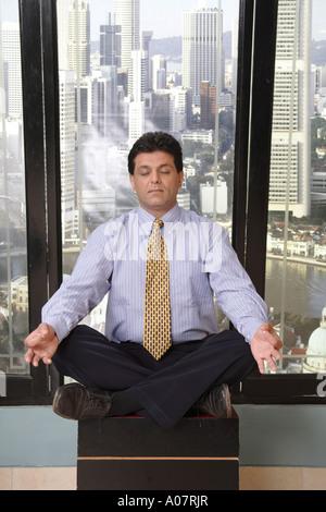 CEO fare yoga per alleviare lo stress nella sua cabina con lo sfondo della città Foto Stock