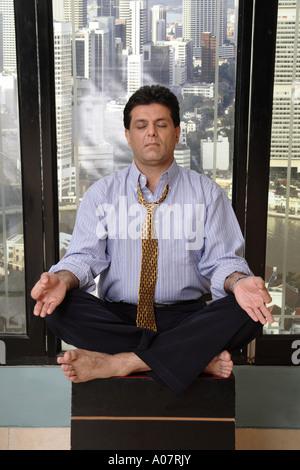 Uomo con esercizi yoga per alleviare lo stress nella sua cabina con lo sfondo della città Foto Stock