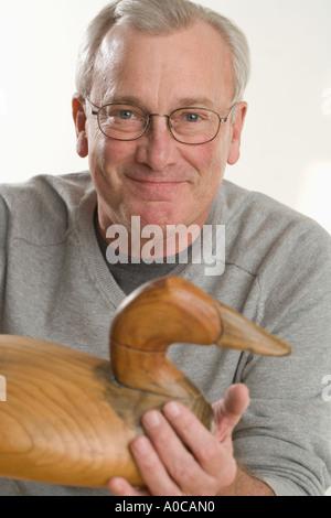 L'uomo azienda artigianale di anatra in legno Foto Stock