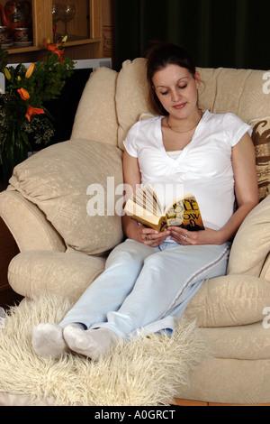 Giovani fortemente incinta Donna con i piedi fino la lettura di libro in poltrona