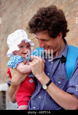 Padre bambino portando la figlia, indossando il simpatico cappello Foto Stock