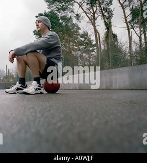 Giovane uomo seduto su un pallone da basket Foto Stock