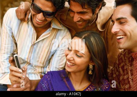Close-up di tre giovani uomini e una giovane donna alla ricerca di un telefono cellulare e sorridente, Agra, Uttar Foto Stock